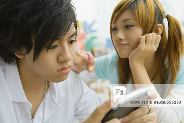 Teenage couple  boy playing video game while girl pesters him