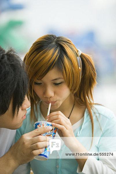 Teenager-Paar  Junge mit Drink für Mädchen