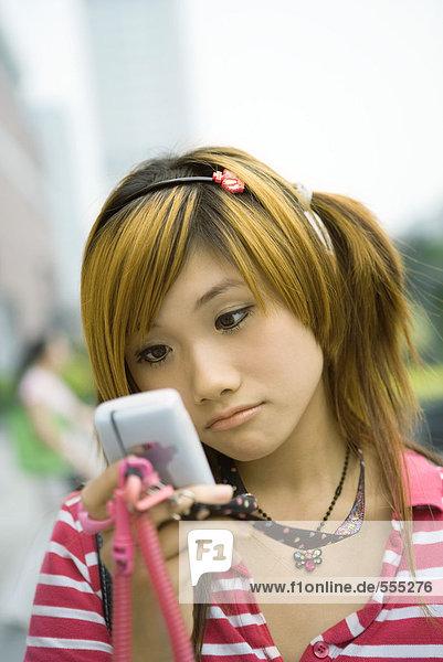 Teenager-Mädchen schaut auf Handy  Stirnrunzeln