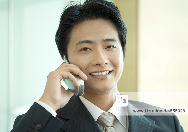 Businessman using cell phone  smiling at camera  portrait