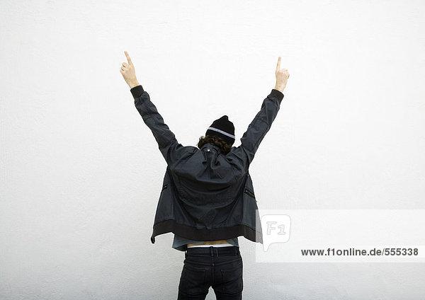 Mann stehend mit erhobenen Armen  mit beiden Händen zeigend  Rückansicht