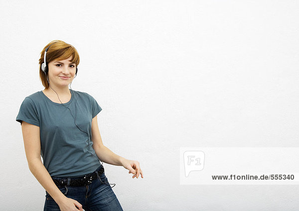 Junge Frau hört Kopfhörer  weißer Hintergrund