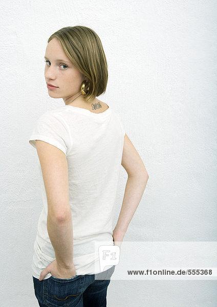 Teenagermädchen stehend mit den Händen in den Gesäßtaschen  Blick über die Schulter auf die Kamera  Rückansicht