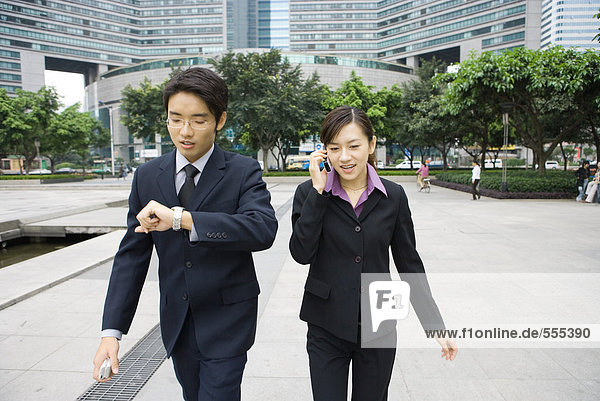 Two young executives walking in office park  one checking watch while other uses cell phone