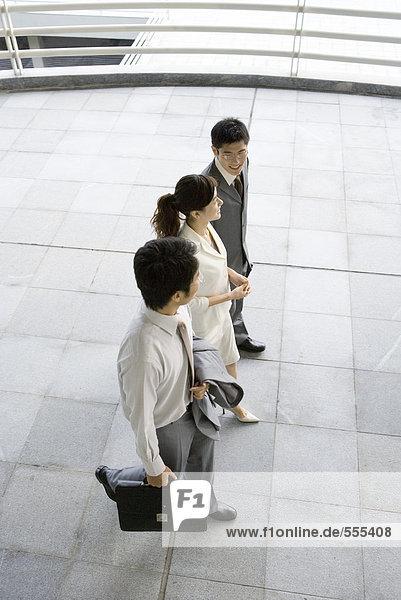 Drei junge Führungskräfte gehen Seite an Seite  hoher Blickwinkel