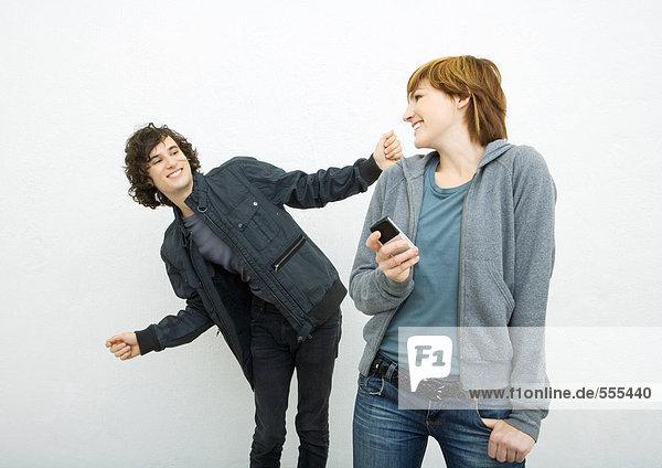 Junge Frau hält Handy  schaut über die Schulter und tanzt einen Freund hinter sich her.