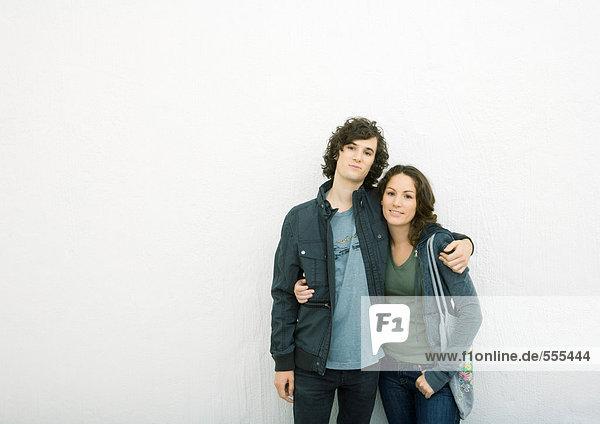 Junges Paar steht mit den Armen umeinander und schaut in die Kamera.