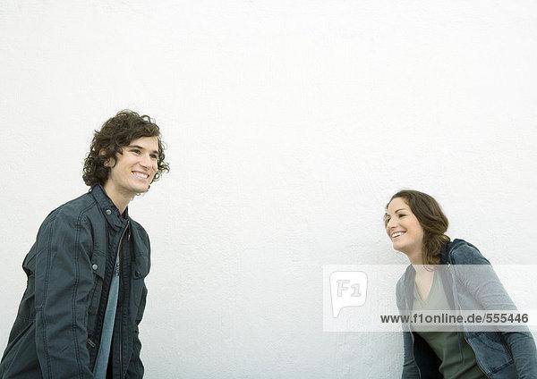 Junger Mann und junge Frau  getrennt stehend  lachend und wegschauend