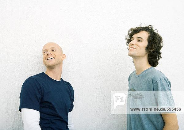 Zwei junge Männer in T-Shirts  die aus dem Rahmen schauen  die Taille hoch.