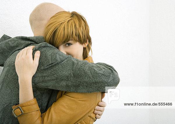 Junger Mann und Frau umarmend  Frau schaut über den Arm des Mannes  schaut in die Kamera
