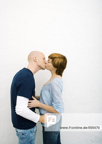 Junges Paar  das sich küsst  Hände auf die Taille.