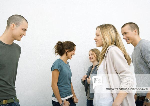 Gruppe von lässig gekleideten jungen Erwachsenen,  die sich aufeinander zu bewegen,  Seitenansicht,  weißer Hintergrund