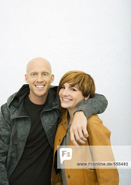 Junges Paar  Mann mit Arm um die Schultern der Frau  beide lächelnd in die Kamera.