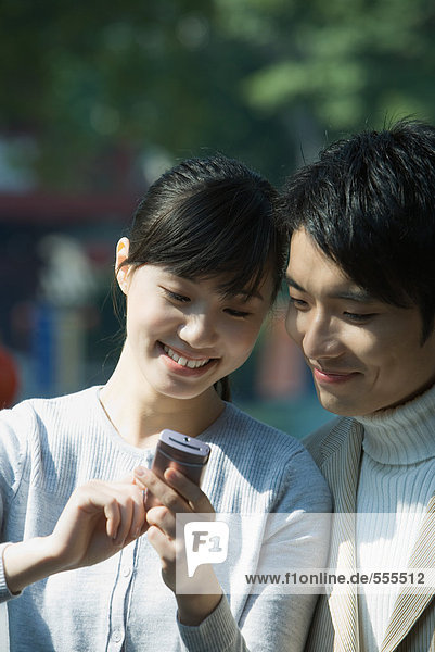 Young couple using cell phone together