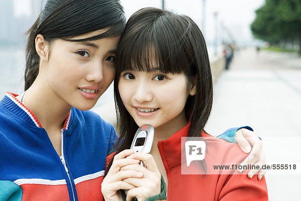 Two female friends  one holding cell phone  smiling at camera