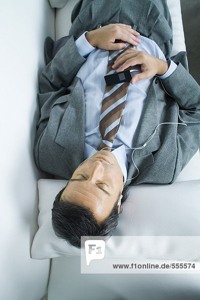 Businessman lying down  listening to earphones