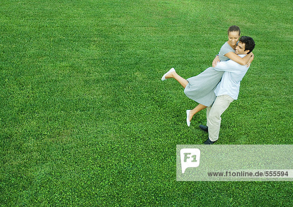 Man swinging woman in his arms  full length  high angle view