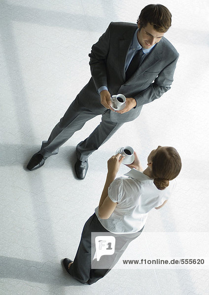 Office employees standing with coffee cups  full length  high angle view