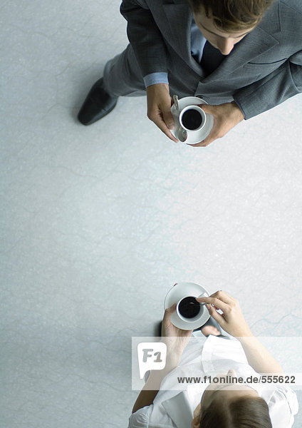 Office employees standing with coffee cups  view from directly above