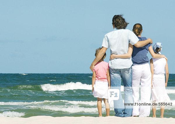 Familie steht neben der Brandung  Blick aufs Meer  Rückansicht