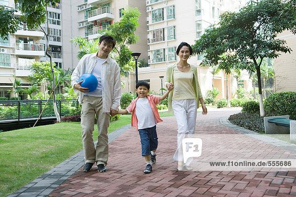 Mutter und Vater gehen mit Sohn und halten Händchen.