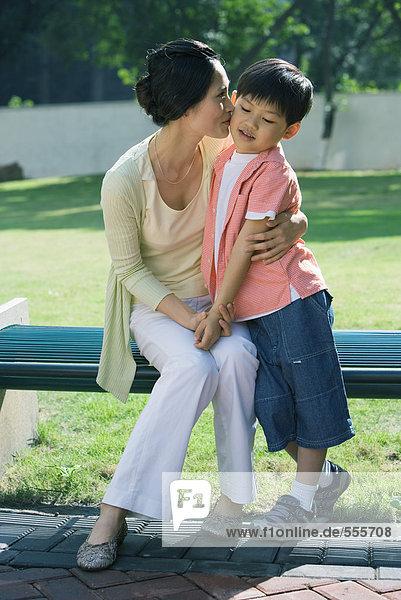 Mutter küssend Sohn auf Wange