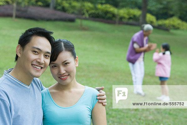 Paar lächelt in die Kamera  Seniorin und Mädchen im Hintergrund