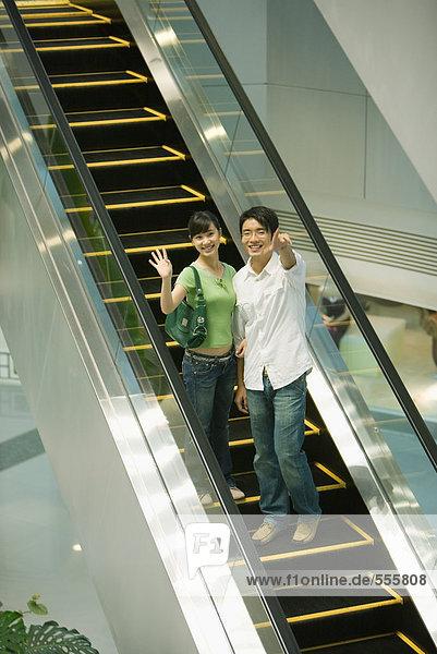 Paar auf der Rolltreppe  das auf die Kamera zeigt