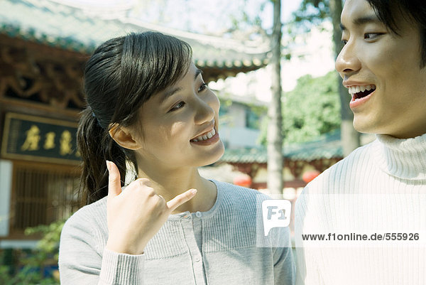 Woman standing next to man  making phone gesture  traditional Chinese building in background