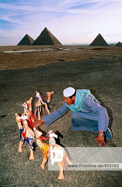 Man selling camels toys at Gizeh pyramids. Cairo. Egypt