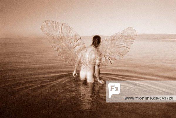 Nackte Mann mit Flügeln zu Fuß in See.