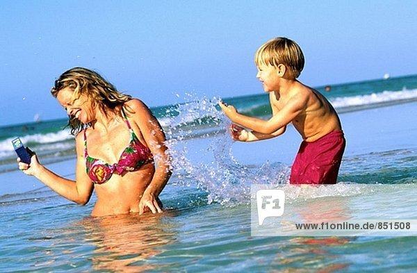 Boy splashing mother