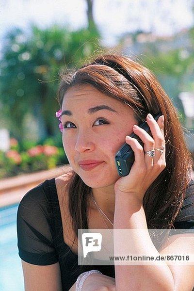 Junge asiatische Frau am Telefon