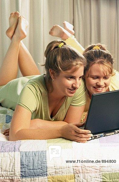 Zwei Freundinnen Verlegung im Bett mit laptop