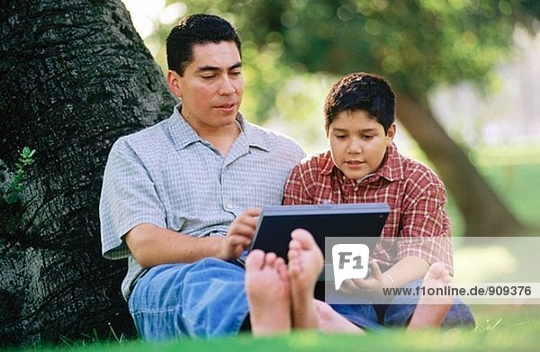 Father and son working on computer