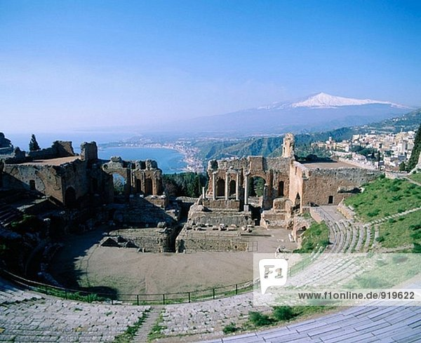 Etna Volcano and ruins of the old Greek theatre. Taormina. Sicily. Italy