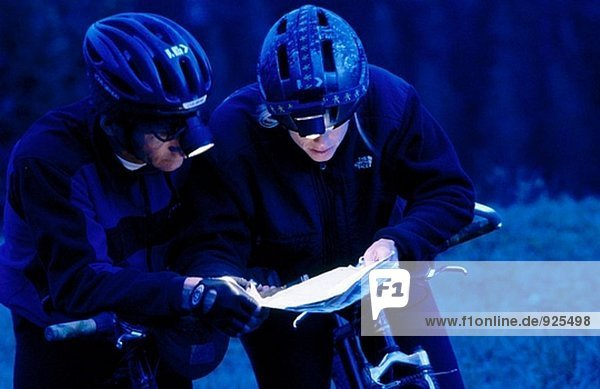 Mountain bikers at twilight with map and headlamps. Alberta. Canada