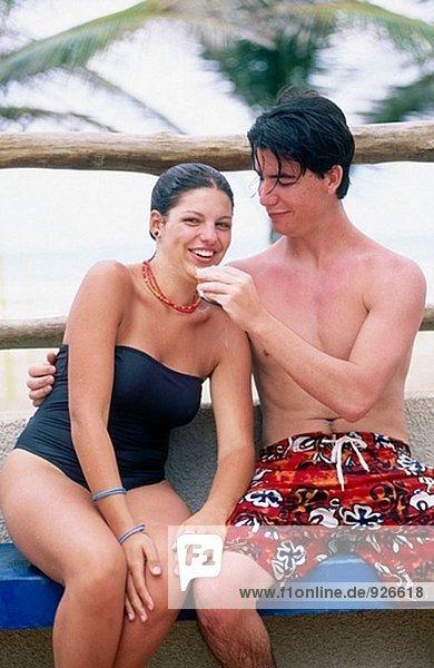 Junges paar auf einer Bank Teilen einen Snack am Strand sitzen
