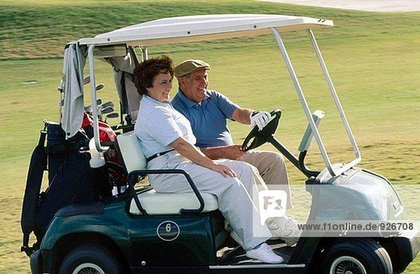 reifes Paar Reiten ein Golf-cart