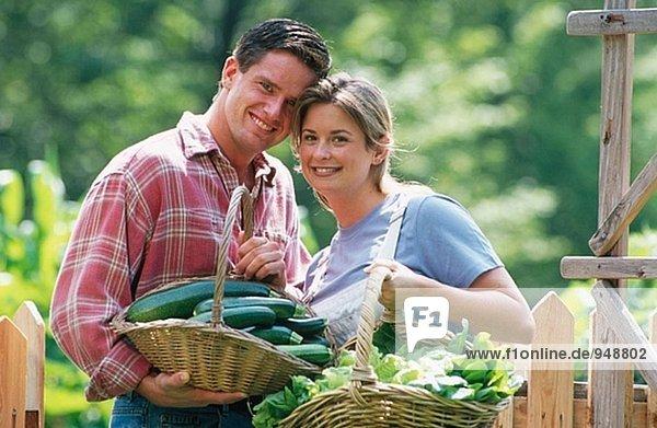 Paar mit Körben von Gemüse