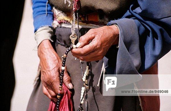 Tibeterin trampen Gebetskette. Litang. Sichuan. Westchina