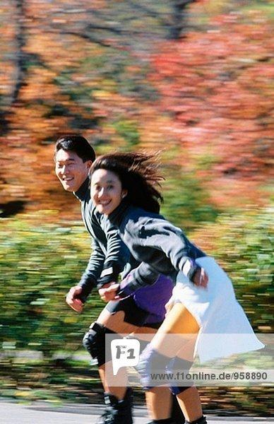 Jungen asiatischen paar Rollerblading im Park im freien