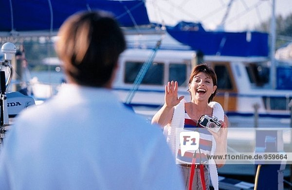 taking a photo of her husband at the marina