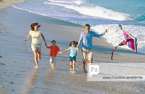 Familie von vier  die entlang der Küste mit einem Drachen