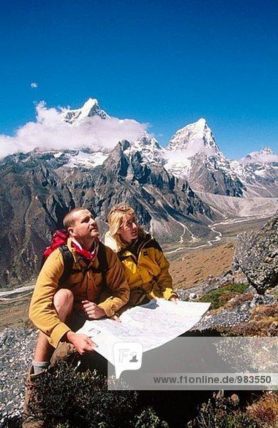 Trekkers mapreading  above Dingboche. Mts. Taweche and Cholatse. Khumbu. Nepal. Himalaya