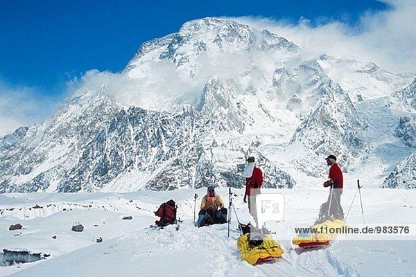 Skifahrer schleppen Schlitten unter Broad Peak  Godwin-Austen-Gletschers. Karakorum  Pakistan