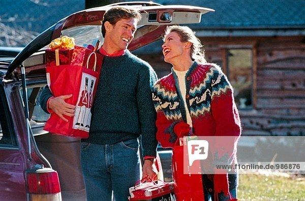 Paar unter Christmas präsentiert Auto