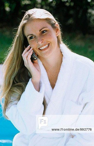 Frau im Bademantel auf Cel Telefon