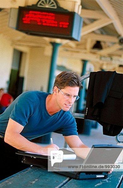 auf einem Computer in einem Bahnhof arbeiten