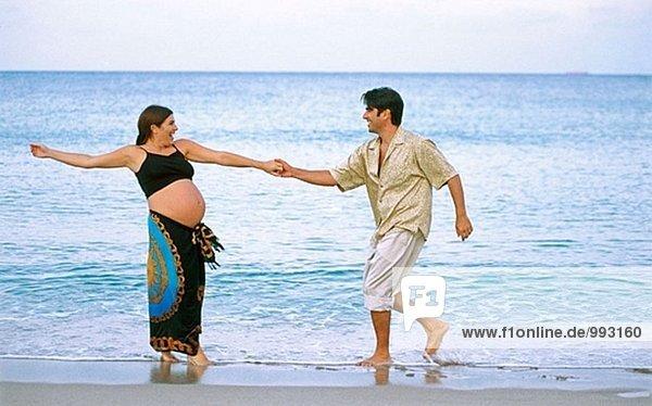 Mann mit seiner schwangeren Frau am Strand
